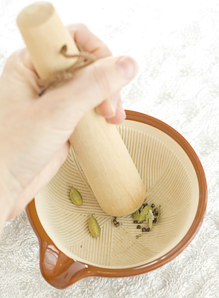 Lightly crush the green cardamom pods with a mortar and pestle