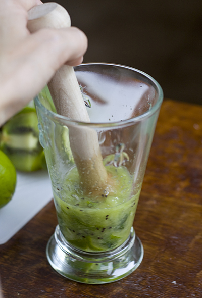 Muddle the kiwi, lime slices, and mint leaves