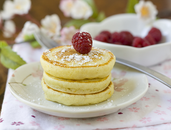 orange mochi pancakes with powdered sugar and fresh raspberries