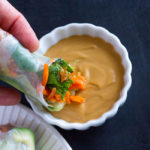 Dipping fresh spring rolls in Easy Peanut Sauce
