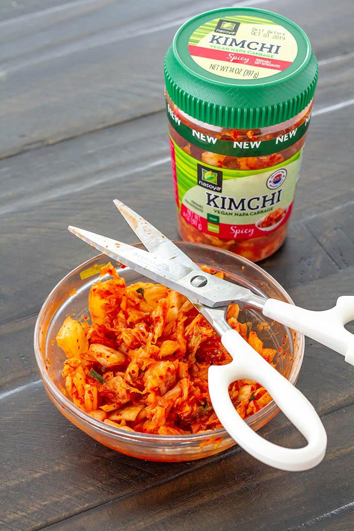 Cutting Nasoya Spicy Napa Cabbage Kimchi with kitchen shears