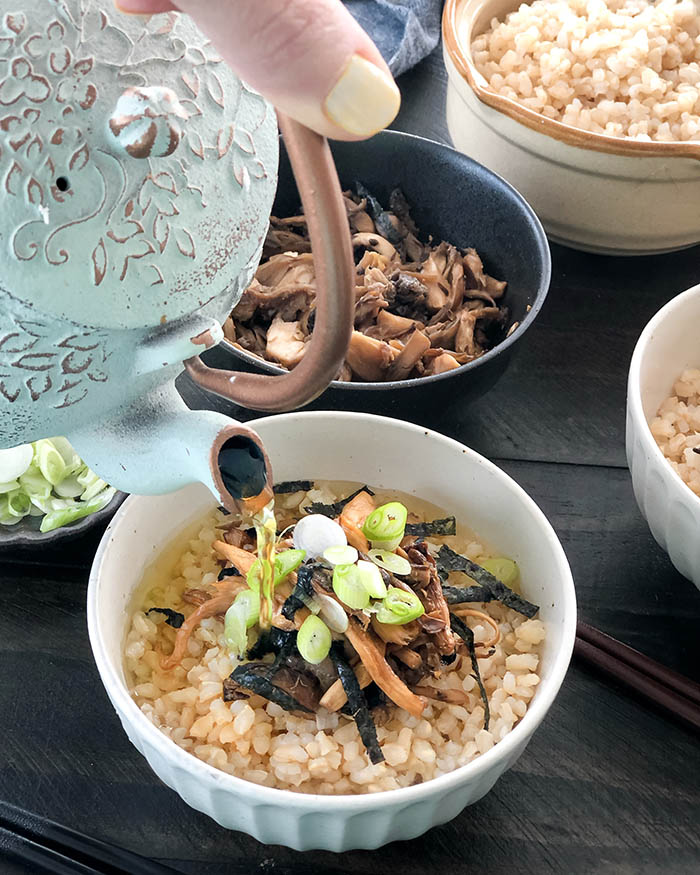 Pouring soba cha over rice and cooked mushrooms