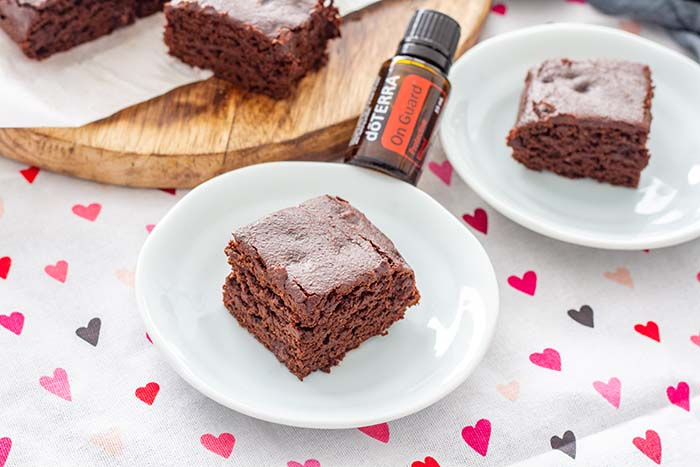Squares of Fudgy Spiced Brownies with a bottle of doTERRA OnGuard oil, which is one of the ingredients