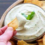 Bowl of lemon basil white bean dip with pita chips